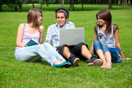 Three students relax and talking on the grass in the park