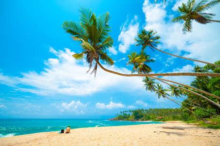 Foto de Tropical beach in Sri Lanka. Young woman sitting on the sand. - Imagen libre de derechos