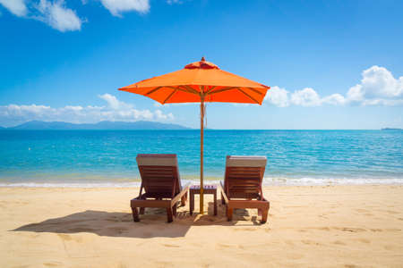 Two lounge chairs with sun umbrella on a beach