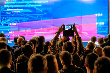 Photo pour Man takes a picture of the presentation at the conference hall using smartphone - image libre de droit