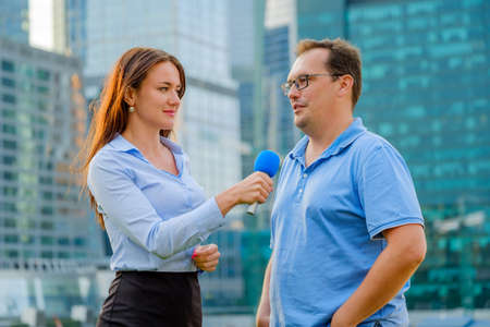 Photo for Young girl TV reporter interviews a man - Royalty Free Image