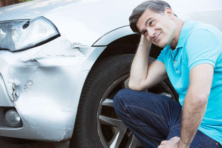 Foto de Unhappy Driver Inspecting Damage After Car Accident - Imagen libre de derechos