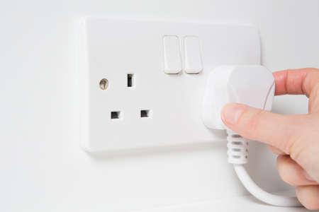 Foto de Hand Putting Plug Into Electricity Socket - Imagen libre de derechos