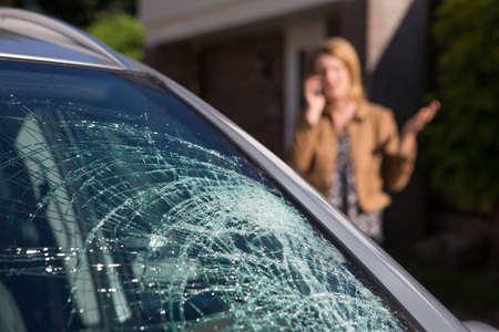 Foto de Woman Phoning For Help After Car Windshield Has Broken - Imagen libre de derechos