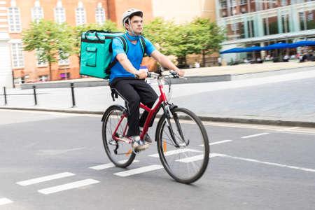 Foto de Courier On Bicycle Delivering Food In City - Imagen libre de derechos