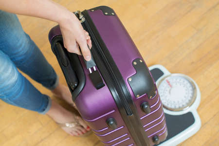 Photo pour Close Up Of Woman Weighing Suitcase On Scale Before Holiday - image libre de droit