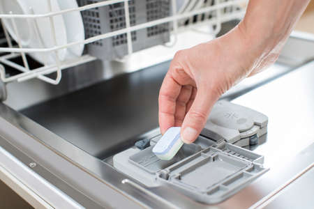 Photo pour Close Up Of Woman Putting Detergent Tablet Into Dishwater - image libre de droit