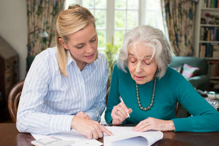 Photo pour Woman Helping Senior Neighbor With Paperwork - image libre de droit