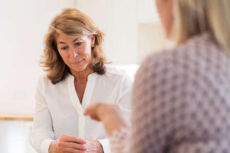 Foto de Mature Woman Discussing Problems With Counselor - Imagen libre de derechos