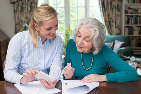 Foto de Woman Helping Senior Neighbor doing Paperwork - Imagen libre de derechos