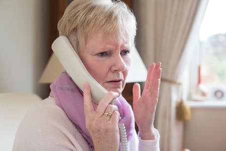 Photo pour Senior Woman Receiving Unwanted Telephone Call At Home - image libre de droit