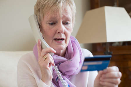 Photo for Senior Woman Giving Credit Card Details On The Phone - Royalty Free Image