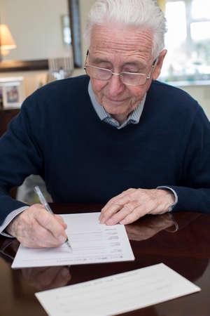 Foto de Senior Man Signing Last Will And Testament At Home - Imagen libre de derechos