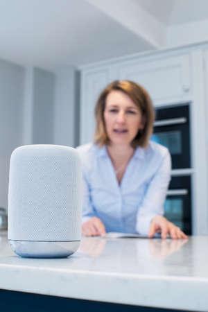 Foto de Woman In Kitchen Asking Digital Assistant Question - Imagen libre de derechos