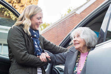Foto per Female Neighbor Giving Senior Woman A Lift In Car - Immagine Royalty Free
