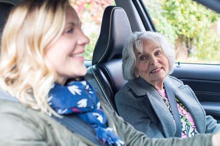 Foto de Female Neighbor Giving Senior Woman A Lift In Car - Imagen libre de derechos