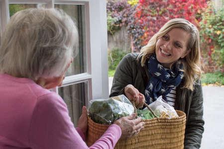 Foto de Female Neighbor Helping Senior Woman With Shopping - Imagen libre de derechos