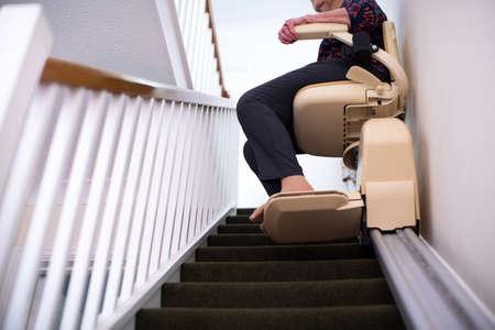 Foto für Detail Of Senior Woman Sitting On Stair Lift At Home To Help Mobility - Lizenzfreies Bild