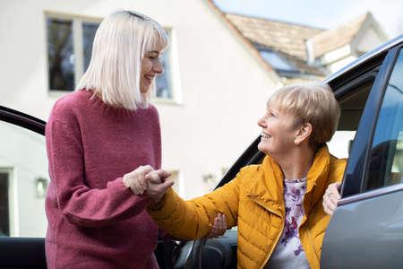 Photo pour Female Neighbor Giving Senior Woman A Lift In Car - image libre de droit