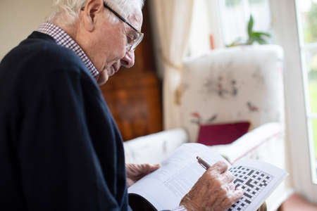 Photo for Senior Man Doing Crossword Puzzle At Home - Royalty Free Image