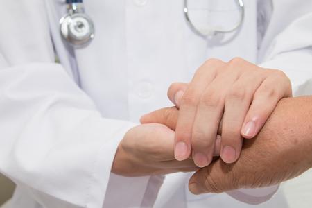 Photo pour Doctor holding an old woman's hand - image libre de droit