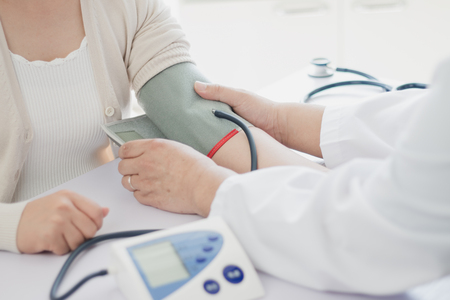 Foto de The doctor measures blood pressure to the patient - Imagen libre de derechos
