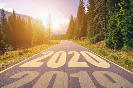 Foto de Empty asphalt road and New year 2020 concept. Driving on an empty road in the mountains to upcoming 2020 and leaving behind old 2019. Concept for success and passing time. - Imagen libre de derechos