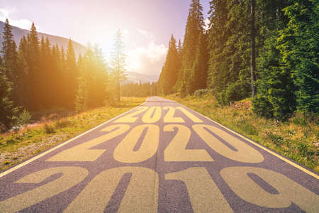 Foto de Empty asphalt road and New year 2019, 2020, 2021 concept. Driving on an empty road in the mountains to upcoming 2019, 2020, 2021 and leaving behind old years. Concept for success and passing time. - Imagen libre de derechos