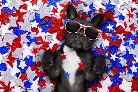 Foto de french bulldog waving a flag of usa and victory or peace fingers on independence day 4th of july with sunglasses - Imagen libre de derechos