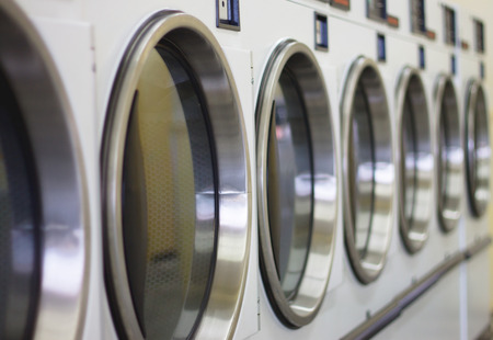 Photo pour laundromat machine washer line with closed doors shallow depth of field - image libre de droit