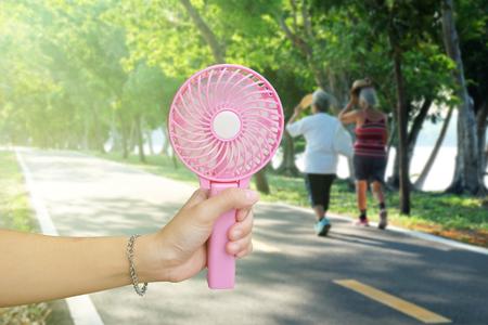 Foto de Hand holding pink portable fan at the public park in summer, hot weather - Imagen libre de derechos