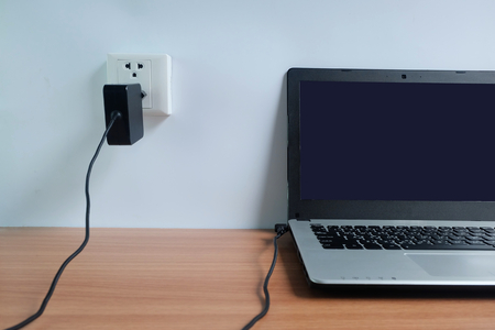 Foto de Plug in power outlet adapter cord charger on a white wall of the laptop computer on Wooden floor - Imagen libre de derechos