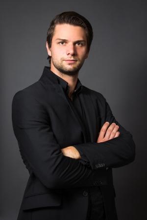 Foto de Man in Black Suit in front of a grey background looking serious - Imagen libre de derechos
