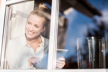 Photo for Young pretty blond woman sitting at the window with her tablet and relaxing in the sun - Royalty Free Image