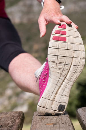 Foto de vibrant image of a feamale doing a hamstring stretch outdoors - Imagen libre de derechos