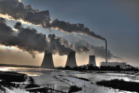 Coal powerplant against sun with several chimneys and fumes