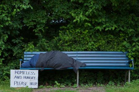 Foto de Homeless man on a park bench with a cardboard sign - Imagen libre de derechos