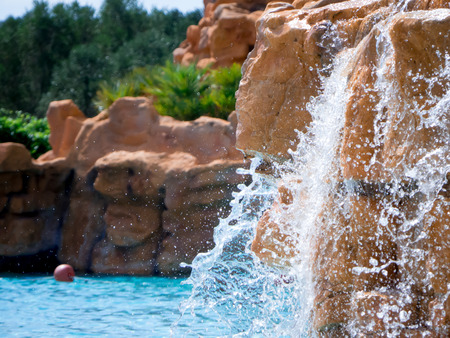 Foto de The water of the pool with a waterfall that comes out of a rocked wall - Imagen libre de derechos