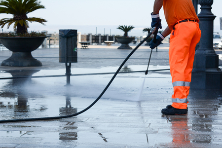 Photo pour a worker with a pressure washer cleaning the street - image libre de droit