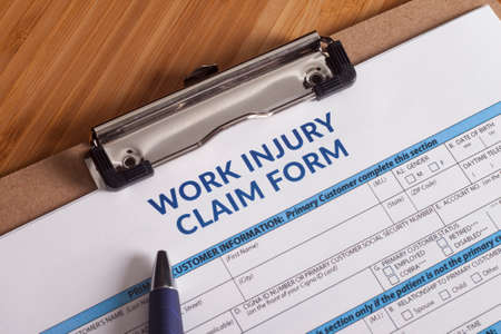 Photo pour Claim form for a work injury on a desk top - image libre de droit