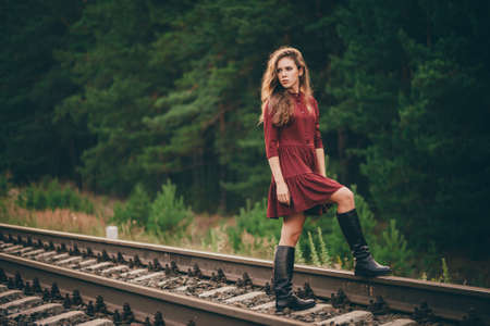 Foto de Beautiful sad thoughtful girl with curly natural hair on nature in forest on railway. Dreamer lady in burgundy dress walk on railroad. Depressed girl on rails at dawn. Sun in hair in autumn. Bad mood. - Imagen libre de derechos