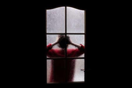 Photo pour Dark silhouette of girl in red behind glass. Locked alone in room behind door on Halloween. Nightmare of child with aliens, monsters and ghosts. Evil in home. Inside haunted house. Supernatural. - image libre de droit