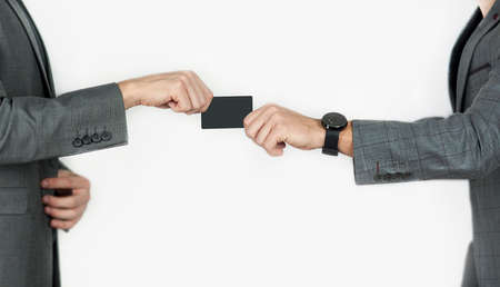 Foto de hands of men transferring a credit card or business card on an isolated background - Imagen libre de derechos