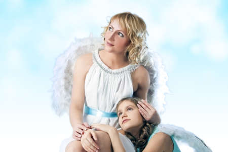 portrait of mother and daughter wearing angels wings together dreaming over artistic background