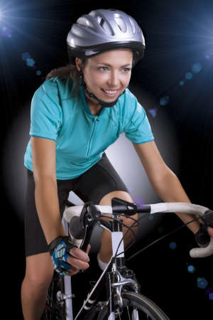 portrait of  woman riding bike over isolated background  model equipped with a professional biking gear, uses professional race bike  vertical shot