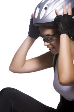 portrait of professional female bike athlete sitting and fixing her protective helmet. vertical image