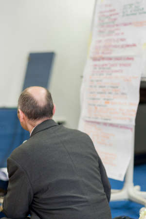 Male Lecturer Sitting in Front of the Long Paper Presentation Sheet. Vertical Image Composition