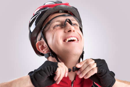 Safety Concept and Ideas. Male Caucasian Cyclist Checking Road Helmet. Wearing Glasses. Against White Background. Horizontal Image
