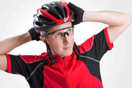 Portrait of Male Caucasian Cyclist Posing in Red Road Protective Helmet and Glasses. Against White Background. Horizontal Shot