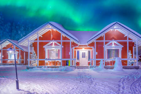 Photo pour Travel Destinations Concepts. Beautiful Multicoloured Vibrant Aurora Borealis known as Northern Lights Playing with Vivid Colors Over Traditional Lapland Houses in Finland.Horizontal Orientation - image libre de droit